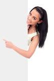 Muchacha sonriente que señala en una tarjeta en blanco Fotografía de archivo libre de regalías