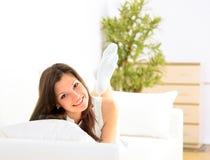 Muchacha sonriente que se acuesta en el diván imágenes de archivo libres de regalías