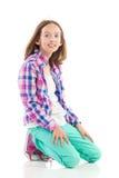 Muchacha sonriente que se arrodilla en el piso Imagenes de archivo