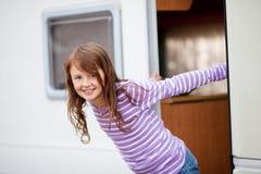 Muchacha sonriente que se coloca en la entrada de la caravana Imágenes de archivo libres de regalías