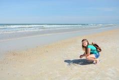 Muchacha sonriente que se divierte en la playa Foto de archivo