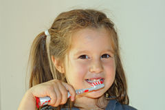 Muchacha sonriente que se lava los dientes blancos Imagen de archivo