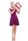 Muchacha sonriente que se pregunta con la actual caja Foto de archivo libre de regalías