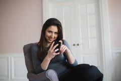 Muchacha sonriente que se relaja en casa, ella está conectando y establecimiento de una red social con su smartphone Imagen de archivo libre de regalías
