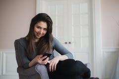 Muchacha sonriente que se relaja en casa, ella está conectando y establecimiento de una red social con su smartphone Fotos de archivo