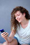 Muchacha sonriente que se sienta con el teléfono móvil que escucha la música Imágenes de archivo libres de regalías
