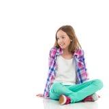 Muchacha sonriente que se sienta con las piernas cruzadas Imagenes de archivo