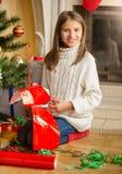Muchacha sonriente que se sienta en el árbol de navidad y cortar el papel rojo para Foto de archivo libre de regalías