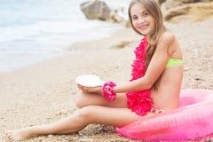 Muchacha sonriente que se sienta en el anillo de goma con las flores Imagen de archivo libre de regalías