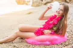 Muchacha sonriente que se sienta en el anillo de goma con las flores Fotos de archivo libres de regalías