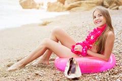 Muchacha sonriente que se sienta en el anillo de goma con las flores Fotografía de archivo