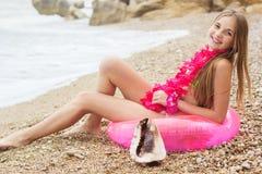 Muchacha sonriente que se sienta en el anillo de goma rosado, verano Fotos de archivo