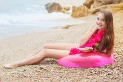 Muchacha sonriente que se sienta en el anillo de goma, tiempo de verano Imágenes de archivo libres de regalías