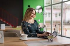Muchacha sonriente que se sienta en el ordenador portátil Foto de archivo