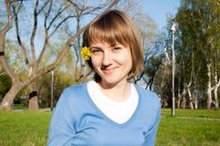 Muchacha sonriente que se sienta en el parque Fotos de archivo