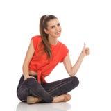Muchacha sonriente que se sienta en el piso y que muestra el pulgar para arriba Fotografía de archivo libre de regalías