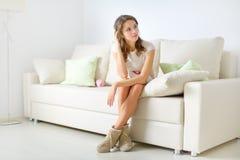 Muchacha sonriente que se sienta en el sofá Imagen de archivo