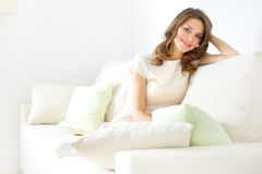 Muchacha sonriente que se sienta en el sofá Imagenes de archivo