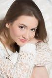 Muchacha sonriente que se sienta en el sofá Imagen de archivo libre de regalías