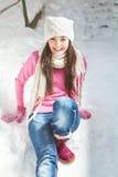 Muchacha sonriente que se sienta en fondo del invierno de la nieve Fotografía de archivo