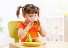 Muchacha sonriente que se sienta en la tabla con las frutas y Imagen de archivo