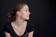 Muchacha sonriente que se sienta en perfil Fotografía de archivo libre de regalías