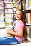 Muchacha sonriente que se sienta en piso cerca del estante Imagen de archivo libre de regalías