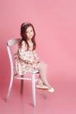 Muchacha sonriente que se sienta en silla en sitio Fotos de archivo
