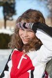 Muchacha sonriente que se sienta en un banco foto de archivo