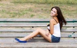 Muchacha sonriente que se sienta en un banco Imagen de archivo libre de regalías