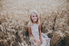 Muchacha sonriente que se sienta en un campo de trigo Fotos de archivo libres de regalías