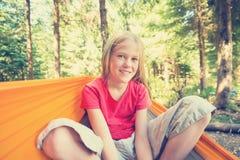 Muchacha sonriente que se sienta en una hamaca Imágenes de archivo libres de regalías