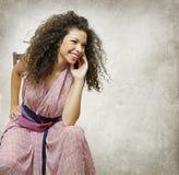 Muchacha sonriente que se sienta en una silla Fotografía de archivo libre de regalías