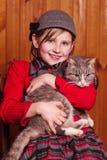 Muchacha sonriente que se sienta en una silla y un gato querido de los abrazos En la granja Imágenes de archivo libres de regalías