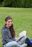 Muchacha sonriente que se sienta a piernas cruzadas Fotografía de archivo