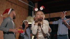 Muchacha sonriente que sopla en confeti multicolor brillante en fiesta de Navidad en oficina almacen de video