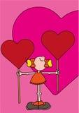 Muchacha sonriente que sostiene dos piruletas rojas gigantes en forma de corazón Imágenes de archivo libres de regalías
