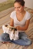 Muchacha sonriente que sostiene el bordado en manos imagenes de archivo