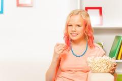 Muchacha sonriente que sostiene el cuenco con palomitas en casa Fotos de archivo