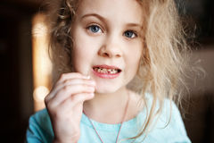 Muchacha sonriente que sostiene el diente de leche que falta, cierre encima de la foto imagenes de archivo
