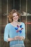 Muchacha sonriente que sostiene el molinillo de viento Imagen de archivo