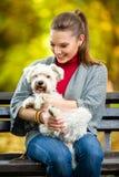 Muchacha sonriente que sostiene el perro maltés lindo Fotografía de archivo libre de regalías