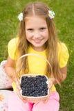 Muchacha sonriente que sostiene la cesta con la baya Imagenes de archivo