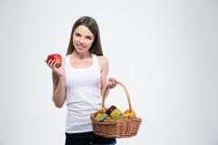 Muchacha sonriente que sostiene la cesta con las frutas Imágenes de archivo libres de regalías