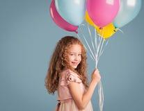 Muchacha sonriente que sostiene los globos Foto de archivo