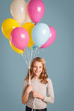 Muchacha sonriente que sostiene los globos Imagen de archivo