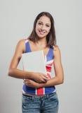 Muchacha sonriente que sostiene un libro Imagenes de archivo