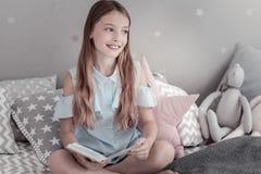 Muchacha sonriente que sostiene un libro mientras que se sienta en la cama Imagen de archivo