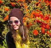 Muchacha sonriente que sostiene un puñado de pasas rojas Fotos de archivo
