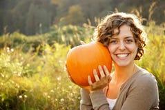 Muchacha sonriente que sostiene un Pumpking Imagen de archivo libre de regalías